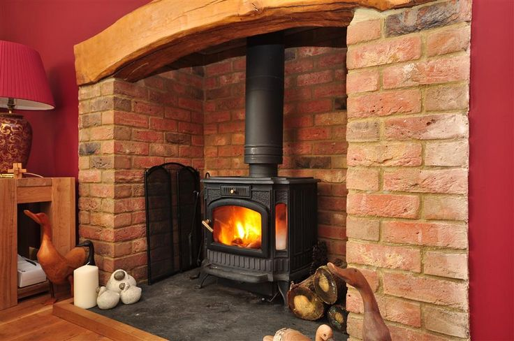 photo of rustic warm red brick with bare floorboards fireplace log burner wood burner