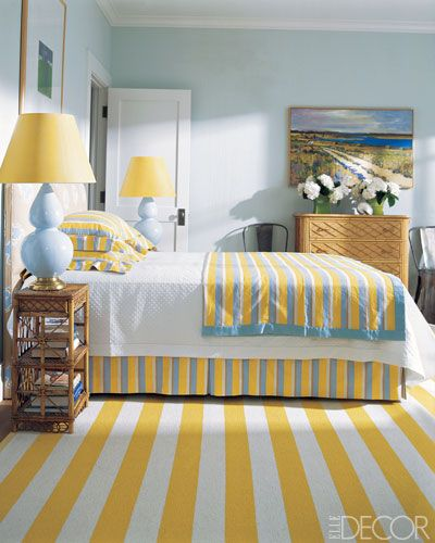 For her familys house in Darien, Connecticut, textile designer Susan Harris decorated a guest room with a vintage French rattan bureau, a Swedish wool rug, and ceramic lamps. The cotton-linen fabrics for the headboard, bedcover, bed skirt, and pillow shams are by Harriss firm, SeaCloth.