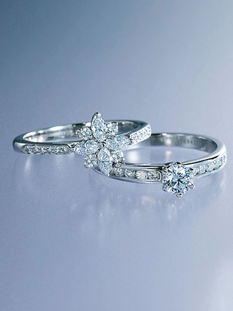 ダイヤモンドの花が咲く華やぎあるエンゲージ(画像上)、愛される花嫁にふさわしい上質な輝きと気品を漂わせて(画像下) ダイヤモンドを花びらのようにデザインした、可憐な一本。「ヴィクトリア クラスター リング」[Pt](ティファニー/ティファニー・アンド・カンパニー・ジャパン・インク)(画像上) アームのダイヤモンドが中央のダイヤモンドを際立てて。「ラウンド&チャネルセッティングエンゲージメント リング」[Pt,中央0.33ct](ティファニー/ティファニー・アンド・カンパニー・ジャパン・インク)(画像下)