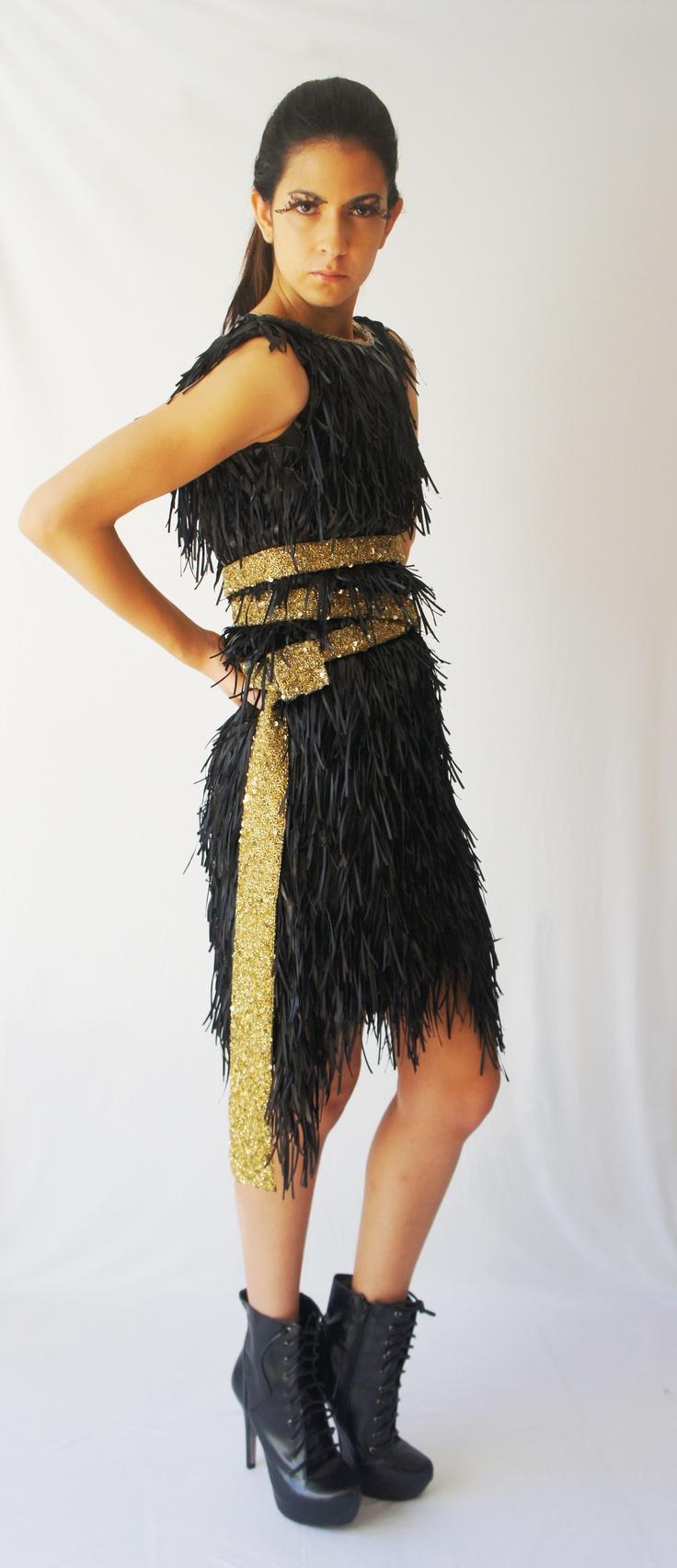 Vestido de bardas con triángulos de simio piel cortados en laser y liston negro cosido simultáneamente, lleva un cinturón de canutillo dorado.