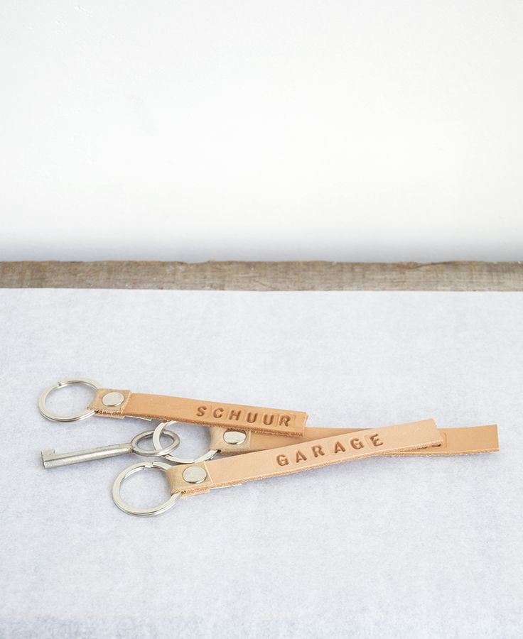 Sturdy leather keyring, with customized tekst stamped into the letter. Send an email with the prefered text (max. 15 letters). shop@olgakorstanje.com  material:	leather, metal colour:		natural, gets darker in use.
