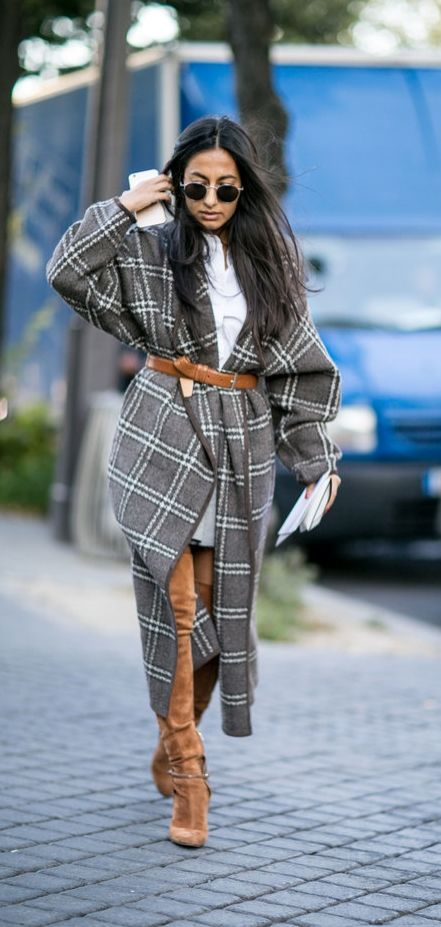 A blanket coat belted with a brown belt and paired with a suede thigh-high