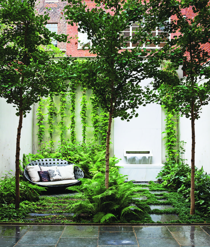 B&B Italia Outdoor's Canasta sofa, by Patricia Urquiola, shares a shady patch in the ground-floor Carnegie Hill garden with three ginkgo biloba trees, an existing fountain with an Italian marble spout designed by Thomas Woltz, and bluestone pavers. The terrace is filled with woodland greenery: Leucothoe, ostrich ferns, and lady ferns.
