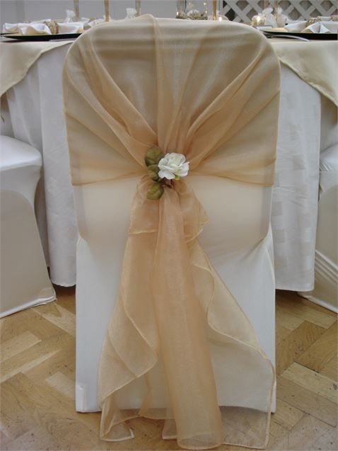 Ivory chair cover with gold organza sash and ivory rose tieback decoration from Pumpkin Events Ltd