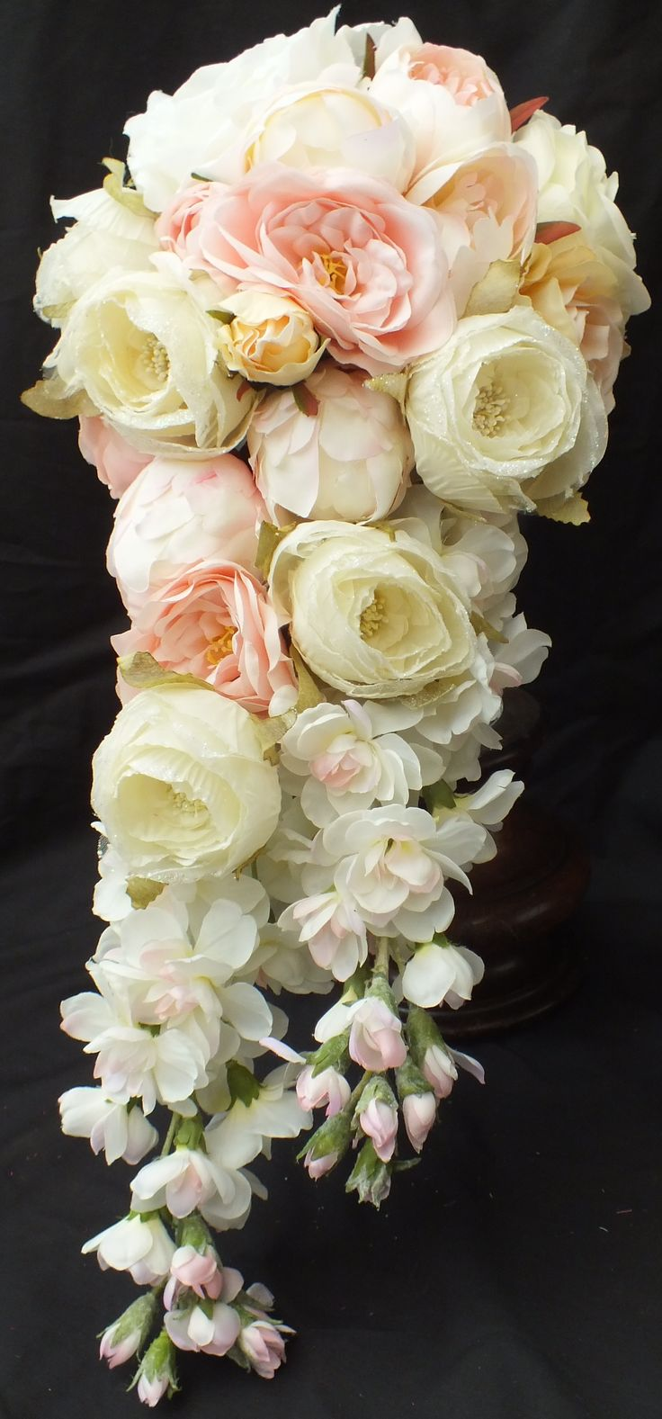 Garden Cascade bouquet with roses, peonies and delphiniums. In shades of white, ivory, pink and peach
