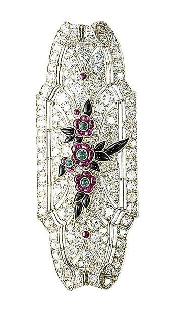 An art deco ruby, onyx and diamond brooch. The tapered rectangular-shaped plaque set throughout with single and circular-cut diamonds, to the central floral motif set with ruby and emerald flowerheads and onyx leaves, mounted in platinum, circa 1925