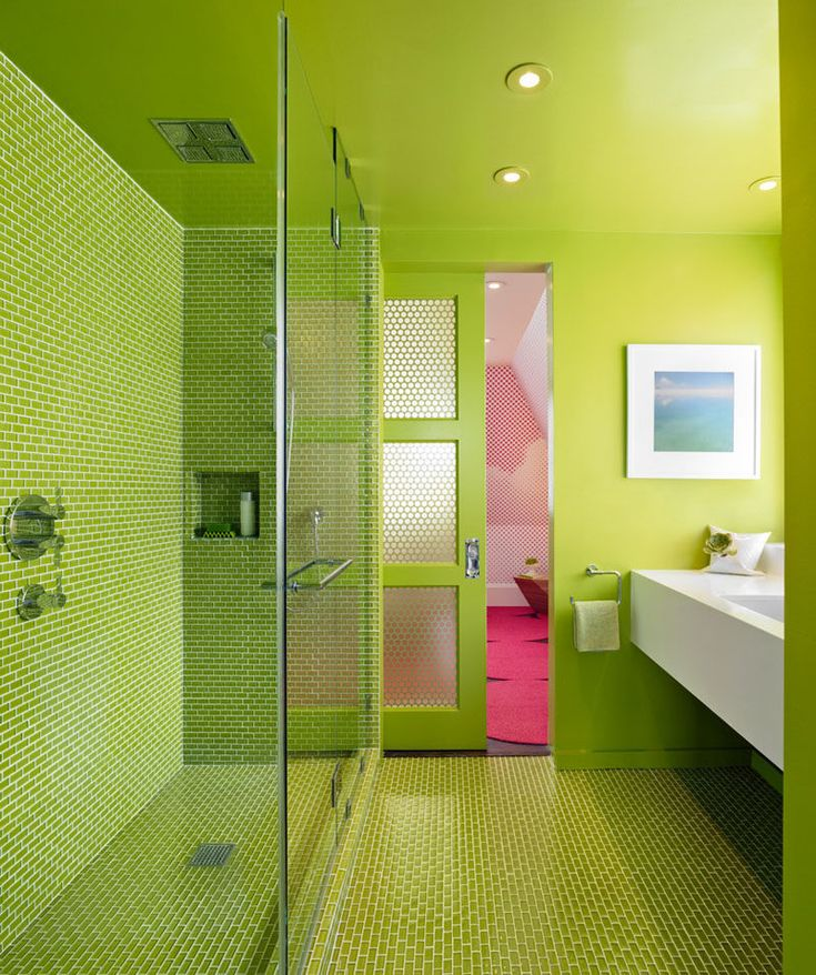 12 Ideas For Including Built-In Shelving In Your Shower // The built-in shelf in this all green bathroom is covered with the same tiles as the rest of the shower and bathroom floor.