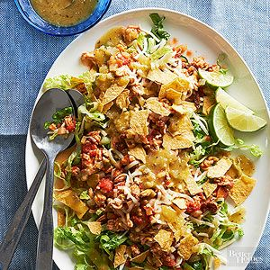 Ground chicken seasoned with coriander and cumin joins canned tomatoes, dried plums, and olives to form the bold mixture that tops this tasty taco salad. Finish with crushed tostada shells and a sprinkle of shredded cheese.