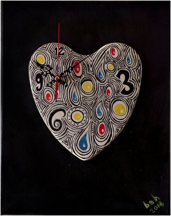 Ceramic heart shaped clock painted and glazed with red, blue, yellow and black on white in tribal like design. The clock is then mounted onto a boxed, stretched canvas painted in black acrylic paint and varnished to keep it in good condition. The canvas is (me).