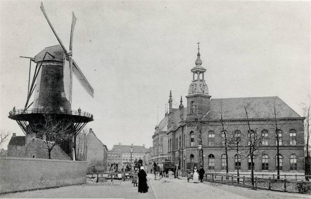 Breda - van Coothplein rond 1900. Links de molen Het Fortuin en rechts de Ambachtsschool. De molen brandde af in 1986, de tegenovergelegen ambachtsschool in 1979. Rivier De Mark (zie hek rechts) stroomde toen nog dwars door de stad.