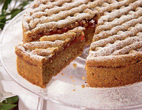 Für den Teig Mehl, Nüsse und Kristallzucker mit Nelkenpulver, Vanillezucker und Zimt vermischt auf ein Backbrett häufen. In die Mitte eine Mulde