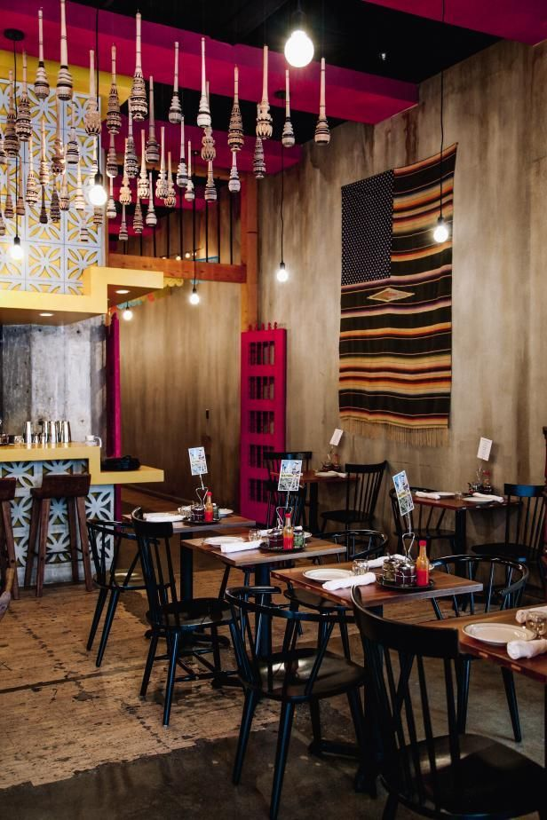 Dining Room of a Mexican Restaurant Featuring Black Spindle Chairs and Repurposed Tables