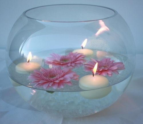Centerpiece similar to this with White Carnations and a White Ranunculus. No floating candles.