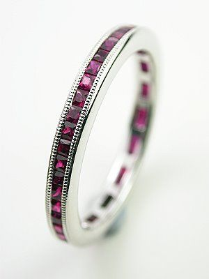 Square Cut Ruby Eternity Band, RG-3061, In this ruby wedding ring, a collection of forty-five square cut rubies winds its way all the way around the 18k white gold anniversary style band. These ruby accents are trimmed in milgrain, a detail that adds textural interest to this eternity band. The rubies have a combined gemstone weight of 1.06 carats. This is a new ruby eternity ring. Size 6.5