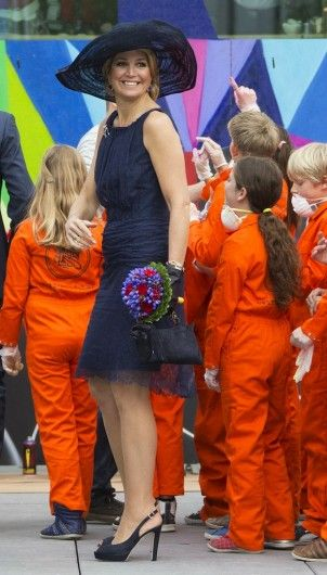 The queen in a dark blue dress and black slingbacks. Click on the image to see more looks.