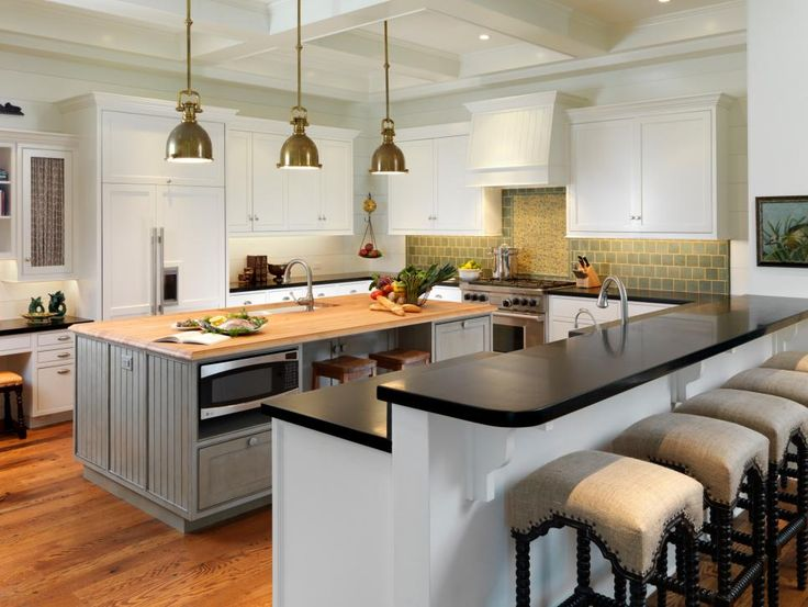 With+two+islands,+lots+of+counter+space+and+an+elevated+breakfast+bar,+this+cottage+kitchen+is+perfect+for+cooking+and+entertaining.+Antique+pendant+lights+illuminate+the+workspace+and+brings+in+an+aged+rustic+look.