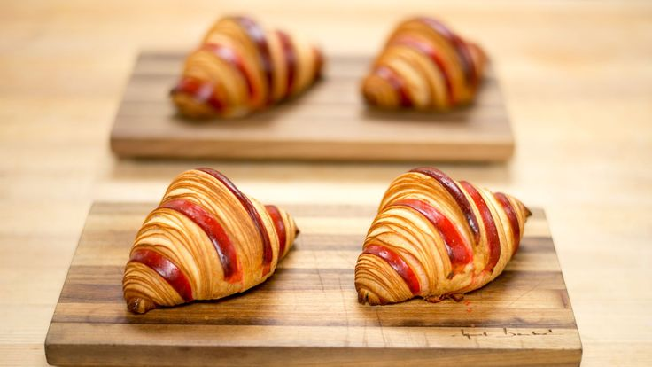 It should be immediately apparent by the clean, geometric lines and bright red candy stripes of dough that the chocolate raspberry croissant at Epicerie Boulud is unlike any other croissant in the...