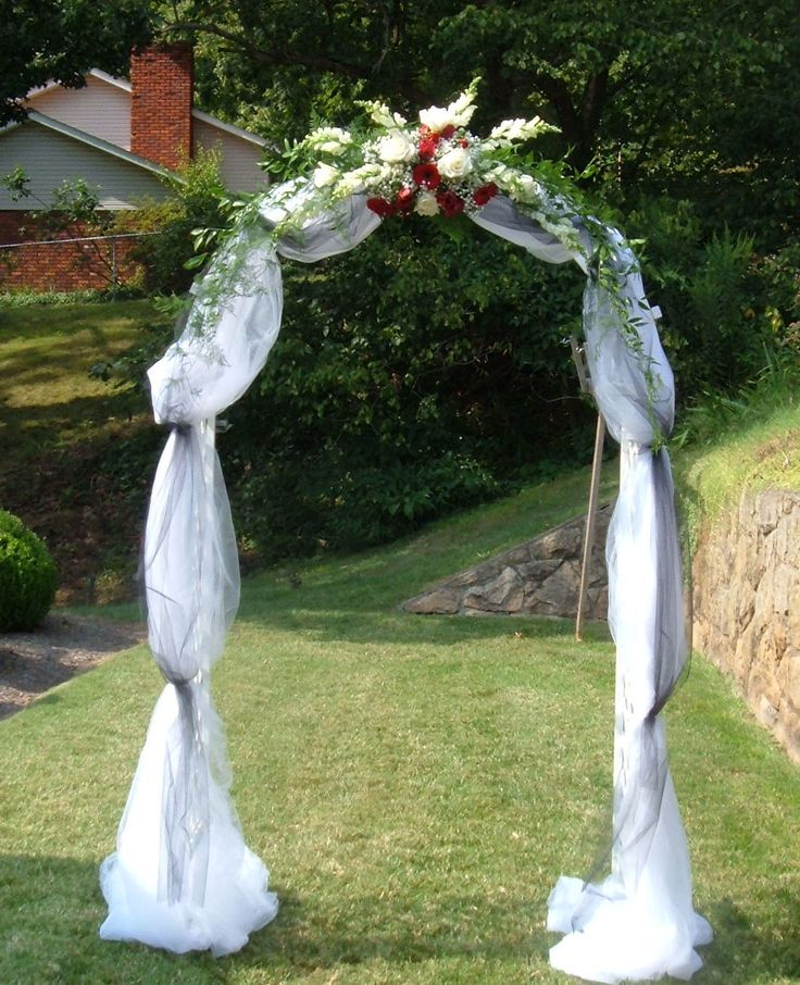 Wedding arch covered with tulle and accented with flowers for Archway decoration ideas
