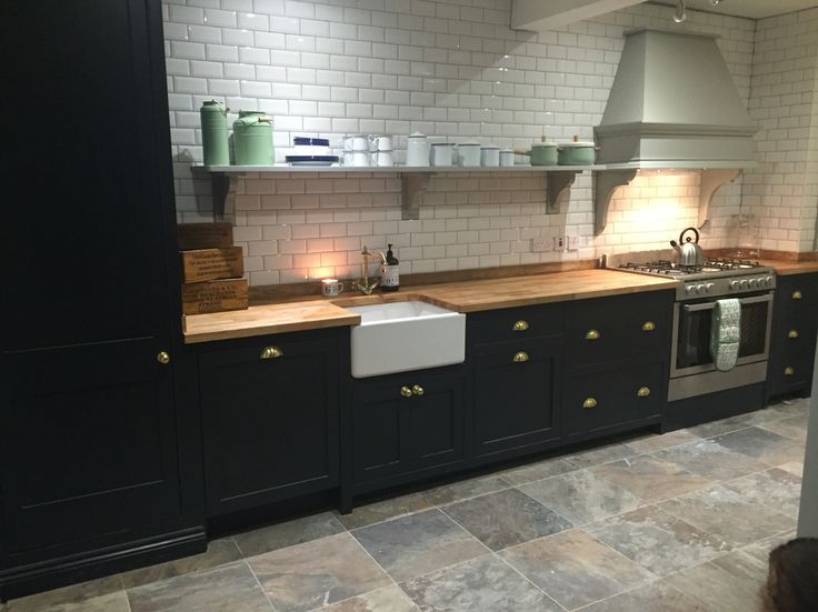 Kitchen with white subway tiles, grey slate floor tiles, open shelving, farrow and ball railings and lamp room grey and Enamelware.