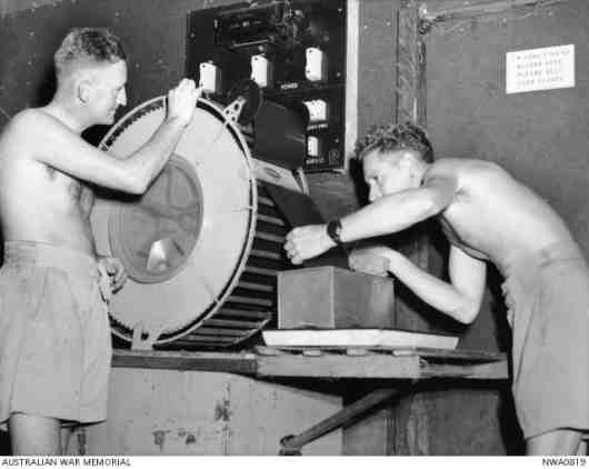 Photographers attached to No. 87 (Photographic Reconnaissance Flight) Squadron RAAF in North Western Australia, are drying a film taken from an aircraft camera