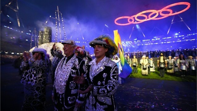 Performers playing Pearly Kings and Queens at the Opening Ceremony take it all in as the Olympic Rings are lifted into place. Over 34,500 buttons were used on the costumes