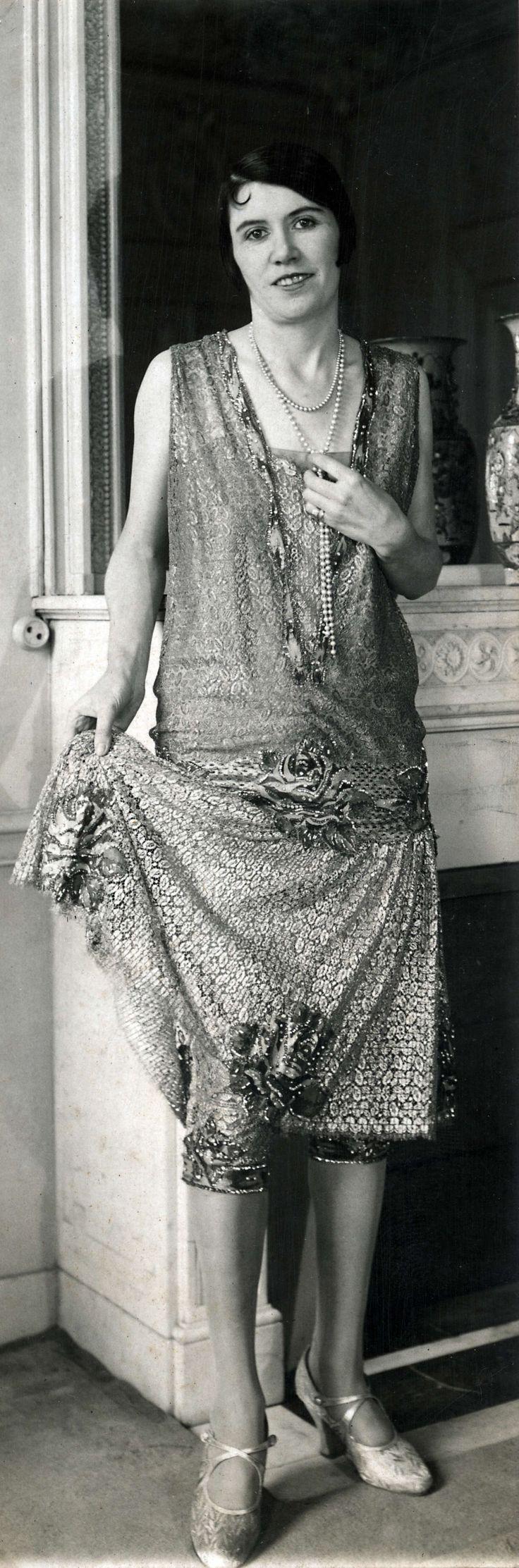14-11-11  Damesmode. Model toont de Parijse wintermode van 1926. Ze draagt een mouwloze avondjapon, rijkelijk bewerkt met kant en bloemmotieven en onder de rok een kniebroek met biesjes. Als sieraad heeft ze een lange ketting om de hals. De creatie is van modehuis Philippe et Gaston. Parijs, Frankrijk, 1926.