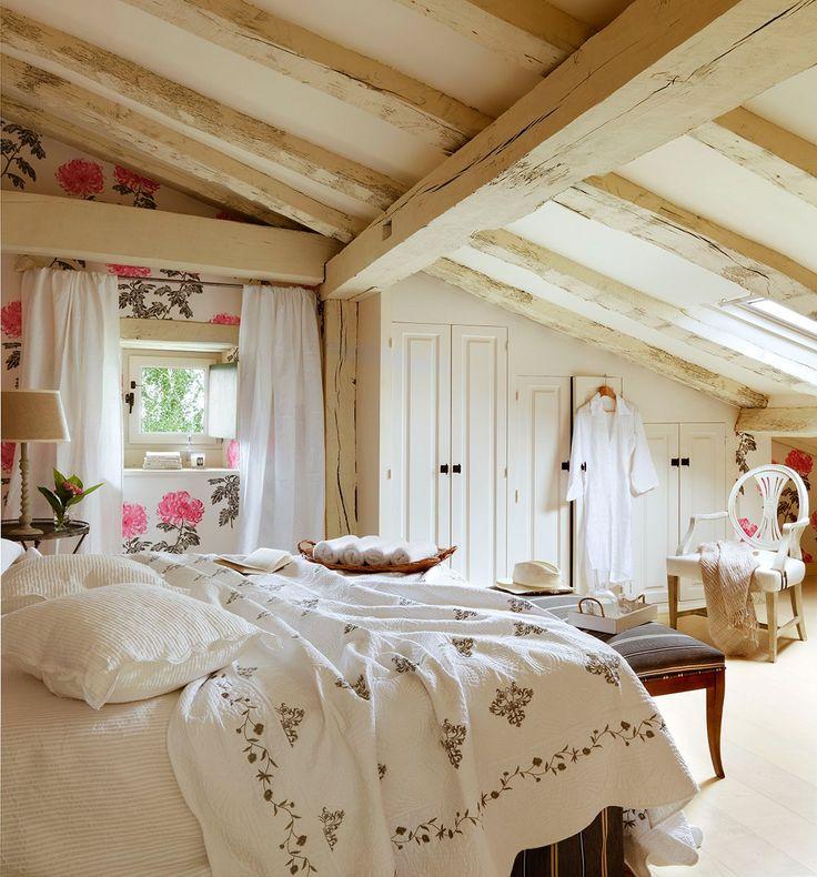 Dormitorio con techo abovedado y papel de pared de flores. Una buhardilla aprovechada