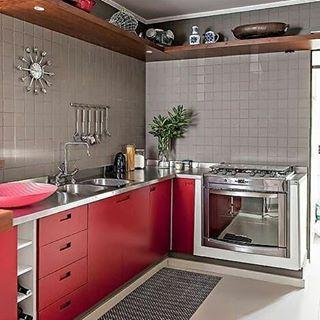 Cozinha com bancada em alumínio, armários vermelhos, acabamento em revestimento cinza e prateleira madeira.