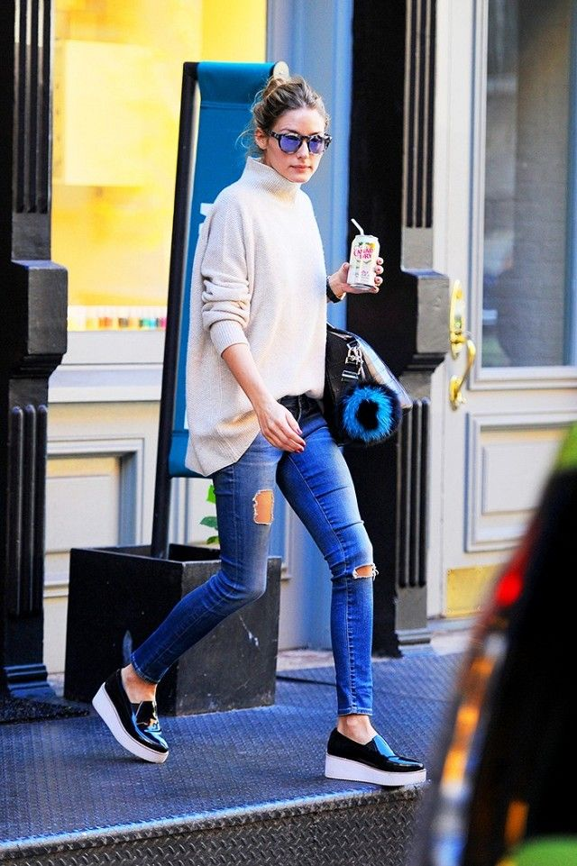 Olivia Palermo wears a turtleneck sweater, distressed skinny jeans, a Givenchy bag, mirrored sunglasses, and platform slip-on sneakers