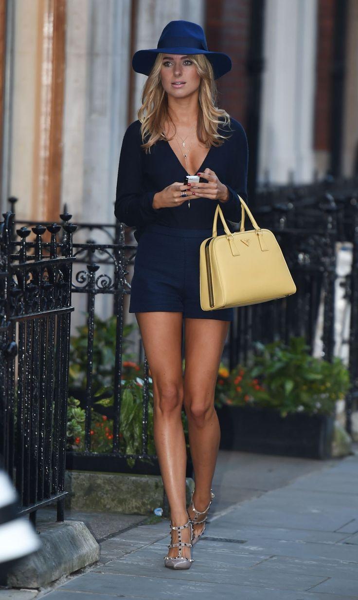 Blue top, shorts hat. Yellow handbag. Long tanned legs. Street apparel. Women fashion