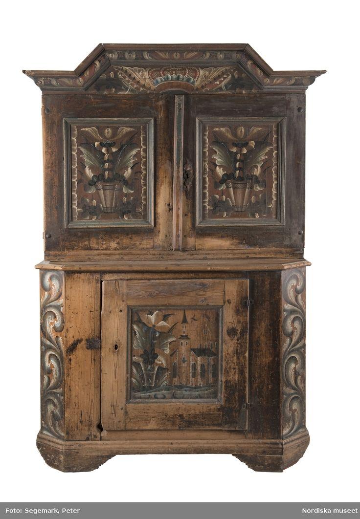 """Katalogkort: """"Skänkskåp i två delar, den nedre m. en enkel dörr, den övre m. dubbeldörrar innanför dessa två hyllor samt skedhylla. Till dubbeldörrarna en nyckel. Märkt: 1783[i avbildande, snirklig skrift]"""""""