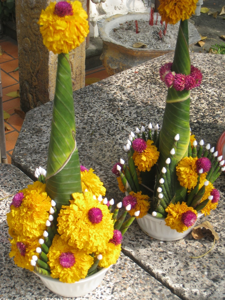 The unique floral arrangements decorate the religious statues in Thailand.