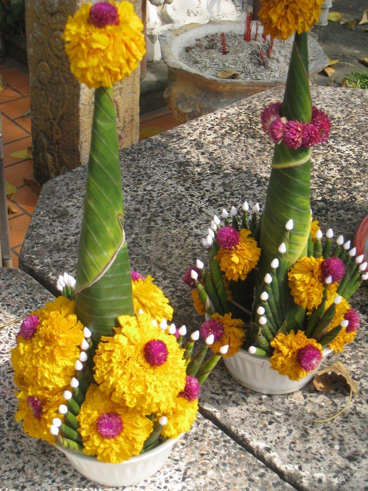 The unique floral arrangements decorate the religious statues in  Thailand.