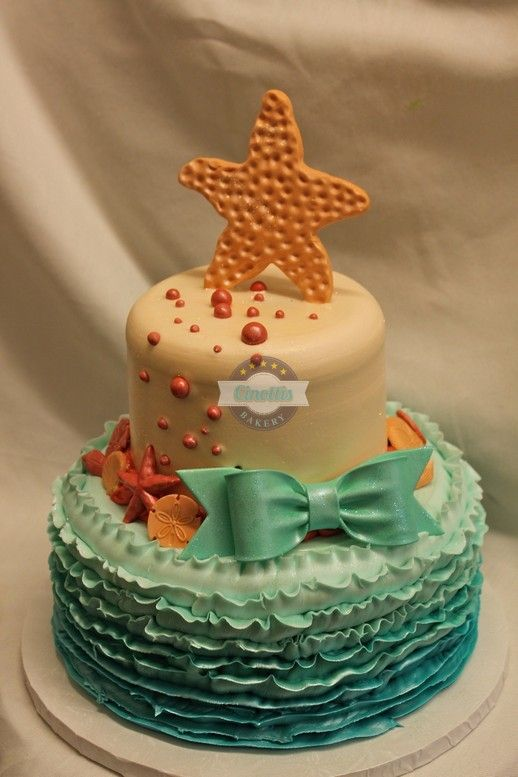 Dusty Mermaid As shown: 9″ and 6″ tiers serving up to 30 Buttercream icing ombre ruffles Fondant Starfish and Shells Gumpaste Bow Candied Pearls Custom Colors Available Glitter Embellishment Please allow 48 hour notice Local delivery and in-store pick up options Please refer to Cinotti's Bakery store policies prior to ordering 11796