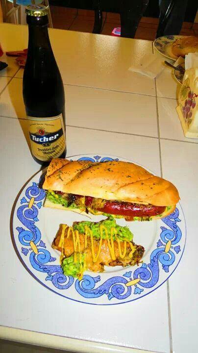 Sandwich con salchicha polaca picante, quesos fundidos y guacamole.