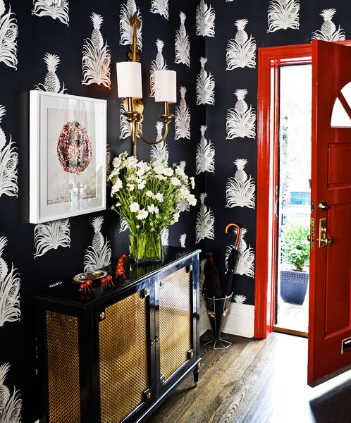 Red front door and foyer with black and white wallpaper with a welcoming pineapple motif