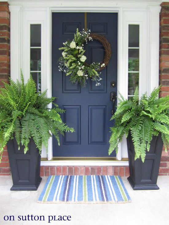 Front porch design with door flanked by ferns and wreath on door