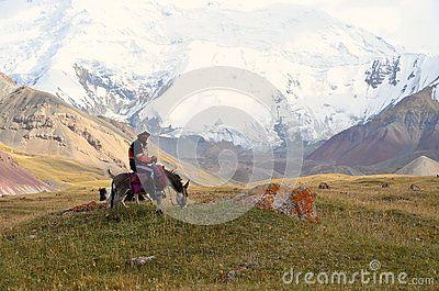 Shepherd sitinig on his donkey.