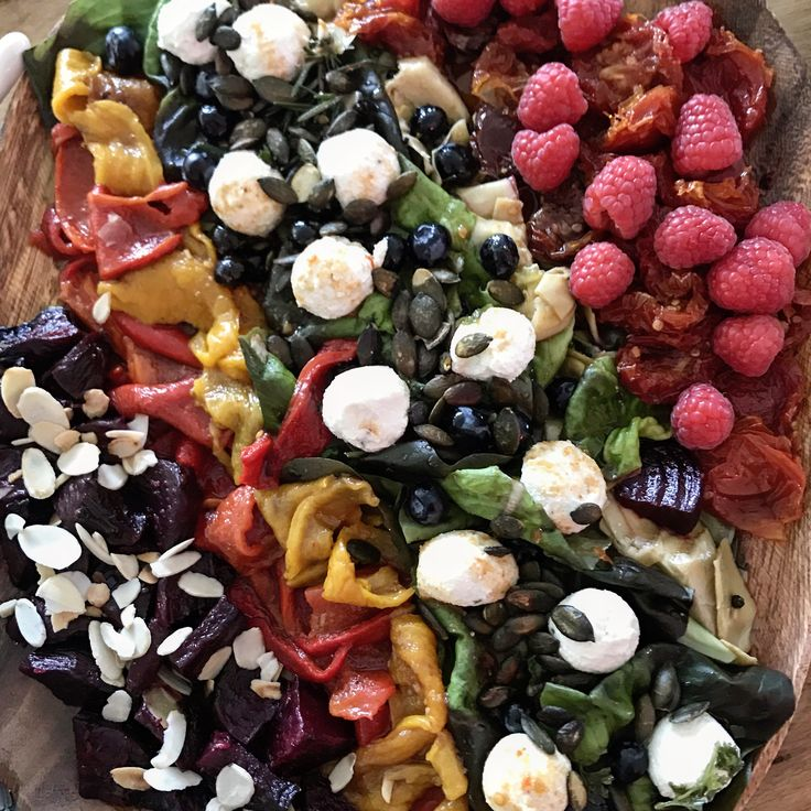 Rainbow salad with beets, artichokes, peppers and sun-dried tomatoes, garnished with pumpkin seeds, blue berries and raspberries