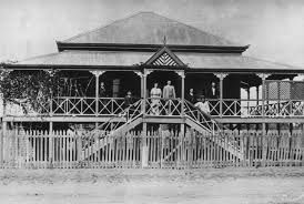 Large Queenslander home in Emerald (Qld) with family gathered on the front veranda c 1912.
