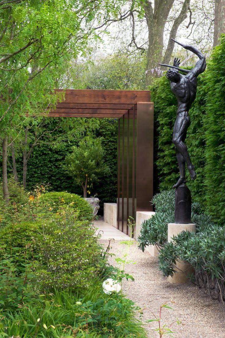 Sleek modern arbor, accented by a harmonious statuary amongst a lavish backdrop.