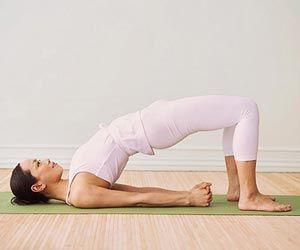 Bridge Pose  Lie on floor with knees bent and directly over heels.  Place arms at sides, palms down. Exhale, then press feet into floor as you lift hips.  Clasp hands under lower back and press arms down, lifting hips until thighs are parallel to floor, bringing chest toward chin. Hold for 1 minute.  Make it easier: Place a stack of pillows underneath your tailbone