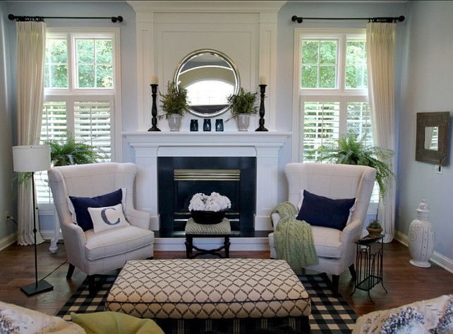 Love the blue wall color with white trim and curtains. And the wing back chairs in front of the fireplace.