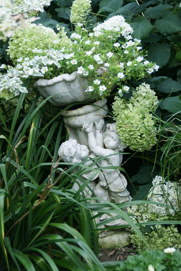 romantyczny biały ogród i jedna z inspiracji , doniczka z aniołami wśród traw wypełniona białymi kwiatami
