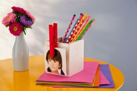Colado na caixa de material escolar, o prendedor também é usado para segurar uma foto - ótima saída para identificar de quem são os objetos da caixinha.