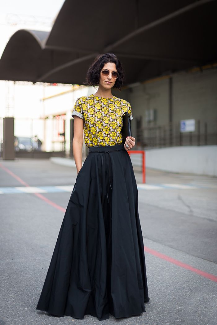 Blusa estampada florida e saia longa preta.