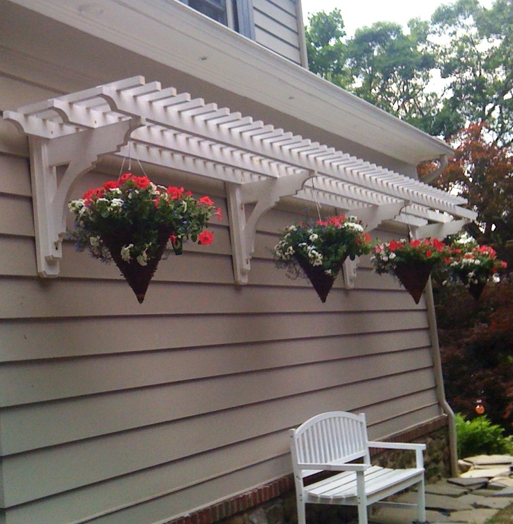 Hanging baskets from a wall arbor creates a restful shaded bench along a path