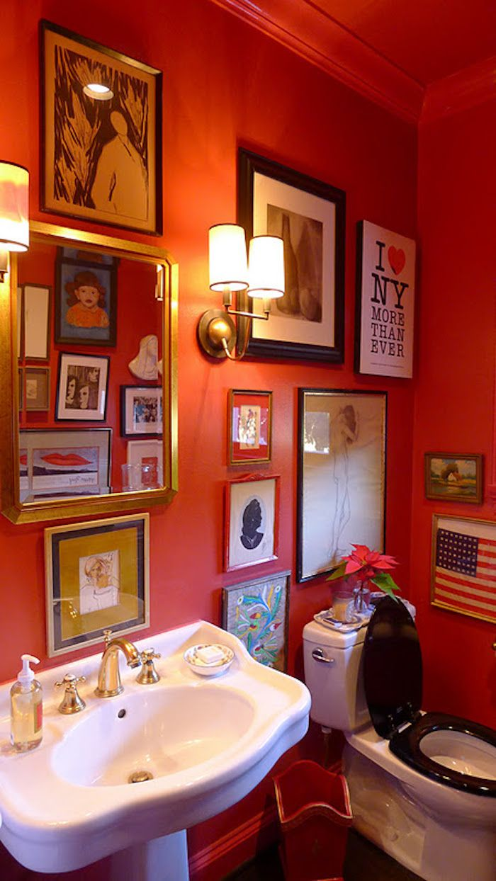 bathroom remodeling, bathroom with vintage black and white toilet, and white antique sink, with red walls decorated with many framed images, wall lights and a red ceiling
