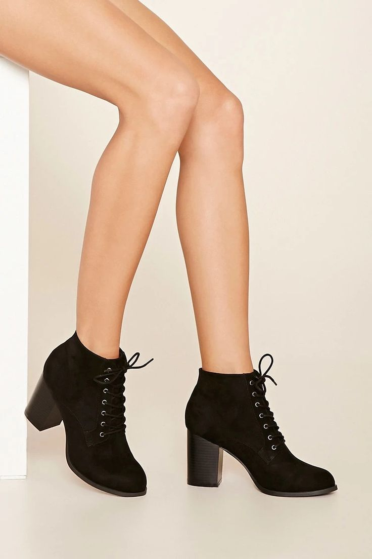 A pair of faux suede ankle booties with a lace-up top and ...