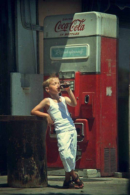 Young boy drinking coca-cola -pose